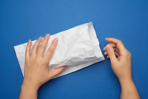 Due mani femminili tengono un sacchetto di carta bianco, zero rifiuti