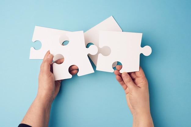 Due mani femminili che tengono i puzzle in bianco bianchi della grande carta su una superficie blu