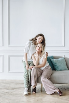 Due modelli femminili in posa vicino al divano in studio nella nuova collezione di vestiti