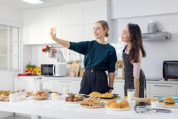 Due amiche si divertono mentre fanno colazione selfie in cucina.