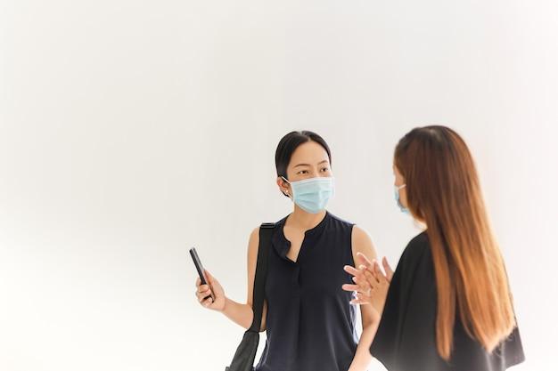 Due donne nella distanza sociale che indossa la maschera per il viso a parlare