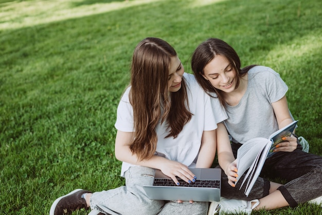 Due studentesse sono sedute nel parco sull'erba con libri e computer portatili, studiano e si preparano per gli esami. educazione a distanza. messa a fuoco selettiva morbida.