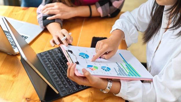 Due studentesse che si consultano sul loro incarico di gruppo con documenti e laptop in biblioteca