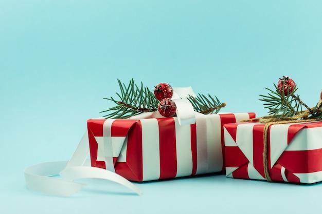 Due regali festivi in confezione rossa e bianca con elementi decorativi di rami di abete e bacche con un nastro bianco. sfondo blu.