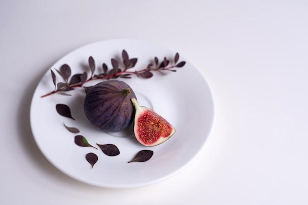 Due fichi su un piatto bianco con un ramo di crespino sul tavolo bianco.