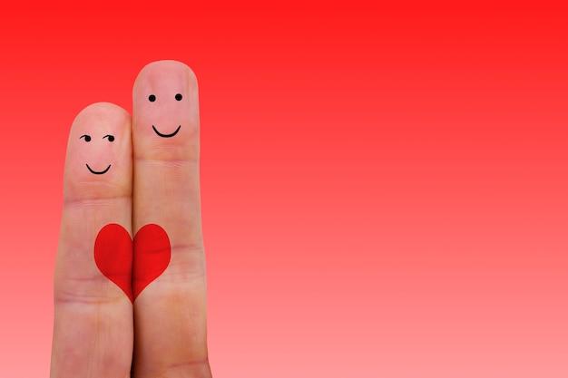 Due dita con i volti di una coppia con sfondo rosso vuoto concetto di amore