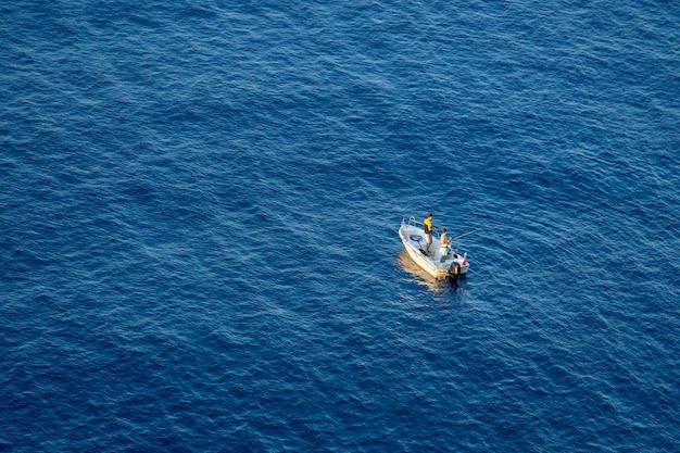Due pescatori stanno pescando da una barca in mare. vista dall'alto.