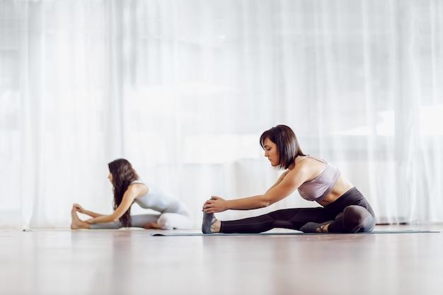 Due ragazze flessibili in forma che si siedono sulla stuoia in studio di yoga e allungano le gambe.
