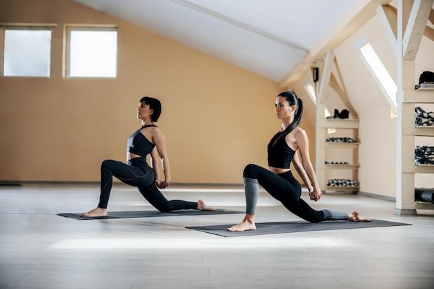 Due donne yogi flessibili in forma nella posa di yoga della lucertola sul ginocchio. interiore dello studio di yoga.