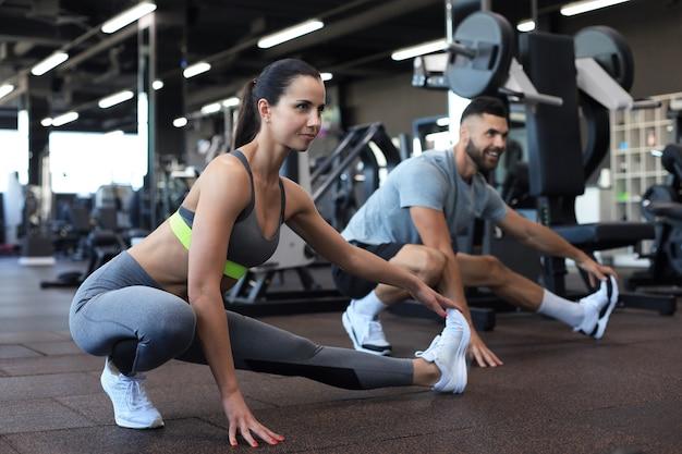 Due persone in forma che fanno esercizi di stretching in palestra crossfit.