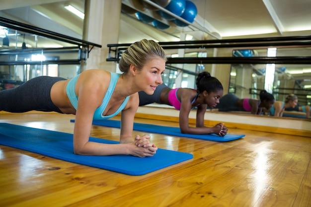 Due donne in forma facendo esercizio di stretching sulla stuoia