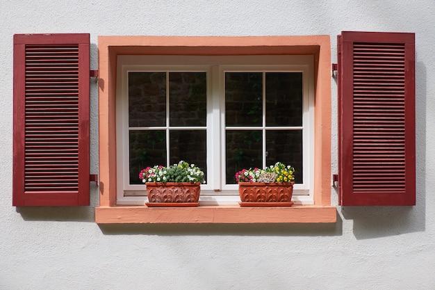 Due vasi di fiori sulla vecchia finestra con persiane in legno sul muro bianco