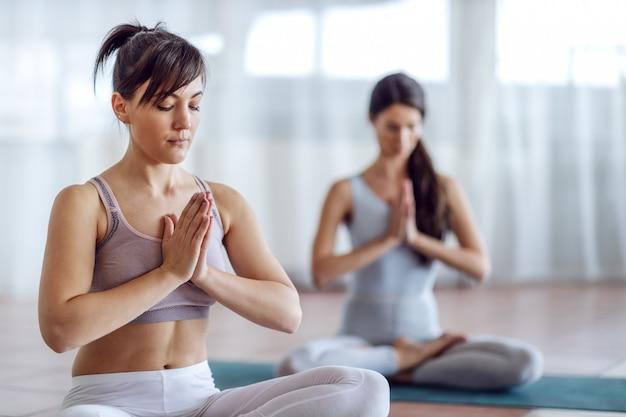 Due belle ragazze yogi messe a fuoco che si siedono nella posa di yoga del loto e che meditano.