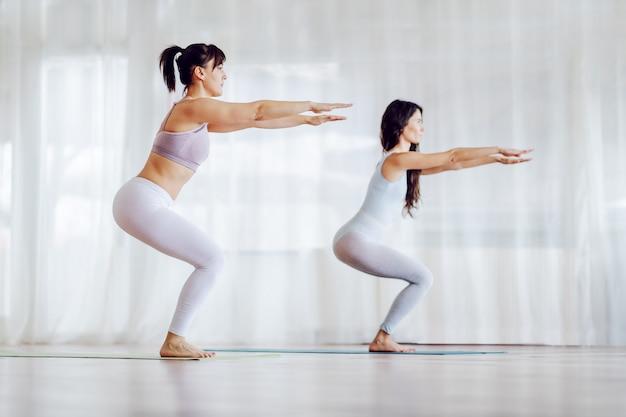 Due ragazze concentrate in forma in posa yoga imbarazzante. interiore dello studio di yoga.