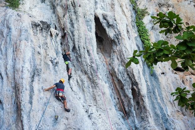 Due uomini stranieri in forma arrampicano su roccia all'isola della grotta di tham phra nang intorno alla spiaggia di railay a krabi