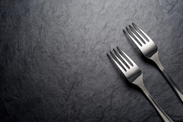 Due forchette su sfondo nero scuro ardesia. vista dall'alto. copia spazio