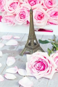 Due fresche rose rosa in fiore posa sulla tavola di legno con la tour eiffel - concetto di viaggio