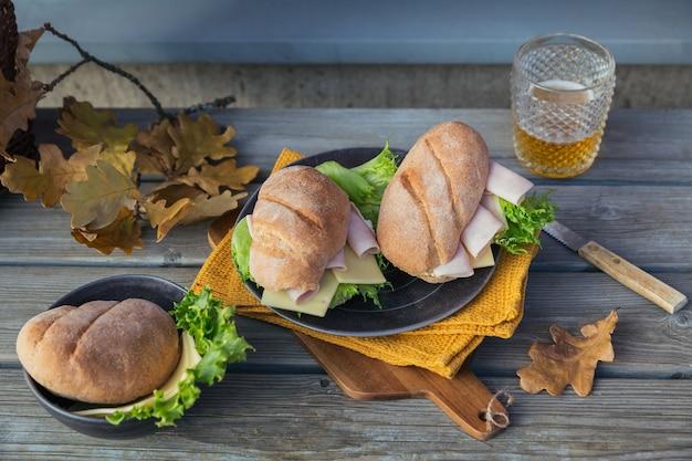 Due panini baguette ciabatta fresca con prosciutto, formaggio, lattuga e un bicchiere di birra su fondo di legno rustico. stile di vita picnic autunnale all'aperto.