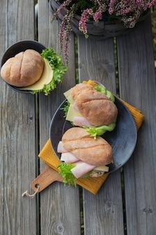 Due panini baguette ciabatta fresca con prosciutto, formaggio e lattuga su fondo di legno rustico. stile di vita da picnic all'aperto. lay piatto