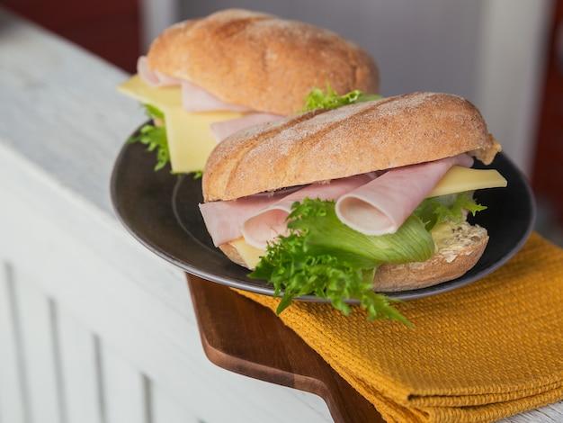 Due panini baguette ciabatta fresca con prosciutto, formaggio e lattuga su fondo di legno rustico. stile di vita da picnic all'aperto.
