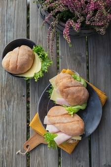 Due panini baguette ciabatta fresca con prosciutto, formaggio e lattuga su fondo rustico in legno wooden