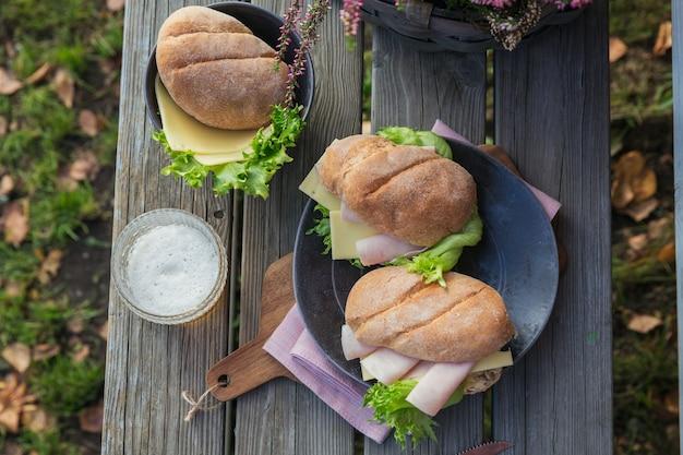 Due panini baguette ciabatta fresca con prosciutto, formaggio e lattuga con un bicchiere di birra su fondo di legno rustico. stile di vita da picnic all'aperto.