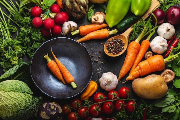 Due carote fresche di fattoria in una ciotola vintage e verdure biologiche assortite su fondo rustico in cemento nero. raccolto autunnale, cibo vegetariano o cucinare un pasto sano e pulito, vista dall'alto