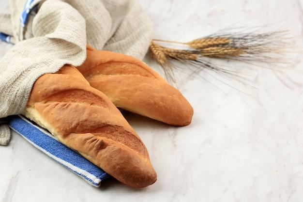Due fresche baguette francesi di pane artigianale su tavolo in marmo bianco con copia spazio per testo o pubblicità