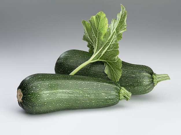 Due zucchine verdi fresche e foglie su uno sfondo bianco. isolato