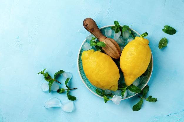 Due limoni freschi nel piatto blu su sfondo di cemento turchese. sfondo di cibo. vista dall'alto.