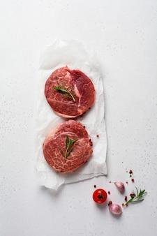 Due fresche parisienne bistecca cruda su carta pergamena bianca con sale, pepe e rosmarino in stile rustico su sfondo di legno vecchio. angus nero. vista dall'alto
