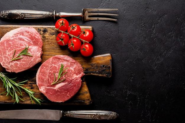 Due fresche parisienne bistecca cruda su tavola di legno con sale, pepe e rosmarino in stile rustico su fondo di legno vecchio. angus nero. vista dall'alto