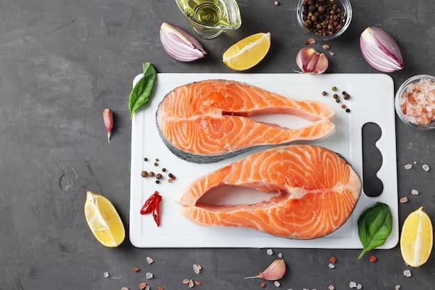 Due bistecche di salmone crudo fresco su tavola di plastica bianca e ingredienti su uno sfondo scuro. spazio per il testo. vista dall'alto