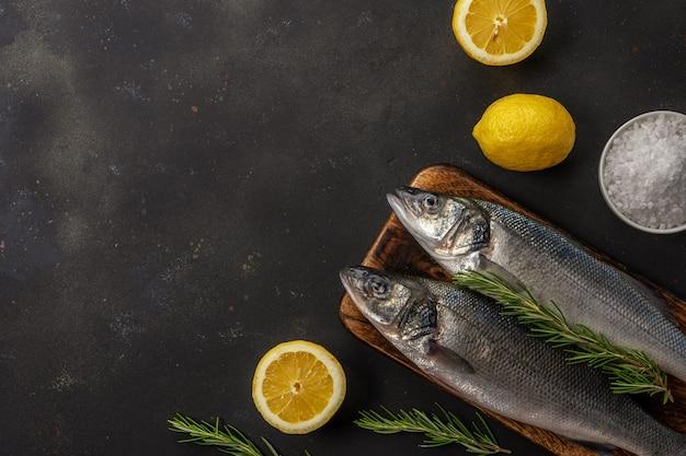 Due pesci freschi della spigola con rosmarino e limone sulla tavola nera
