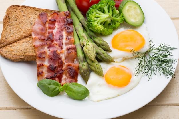 Due uova fritte e pancetta per una sana colazione. messa a fuoco selettiva