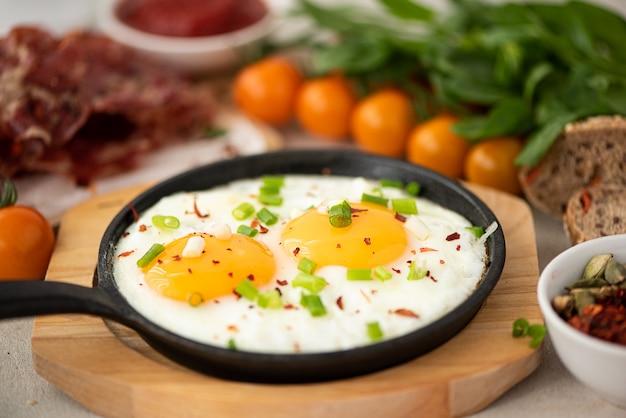Due uova fritte con erbe e spezie in una piccola padella Foto Premium