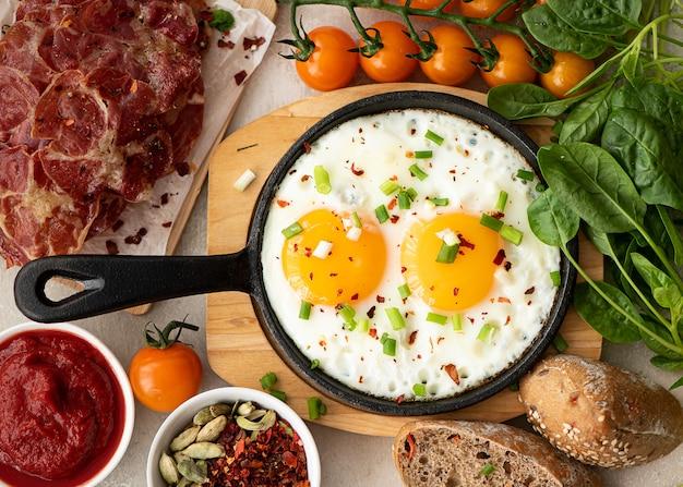Due uova fritte con erbe e spezie in una piccola padella