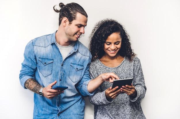 L'amico due si rilassa insieme la tecnologia di uso dello smartphone che controlla i apps sociali sulla parete della parete concetto di comunicazione