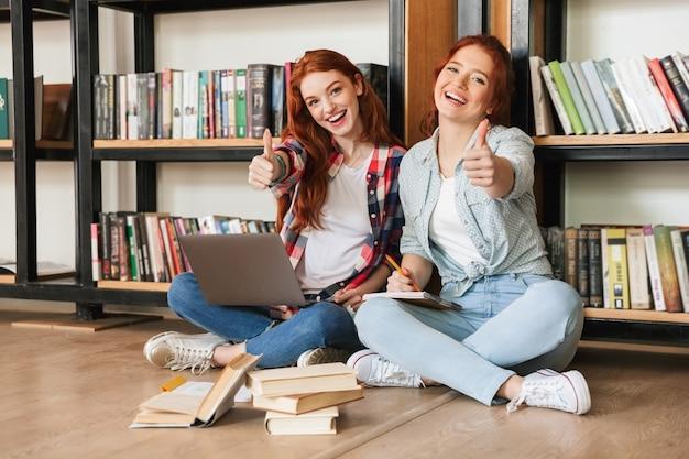 Due amichevoli ragazze adolescenti seduti su un pavimento
