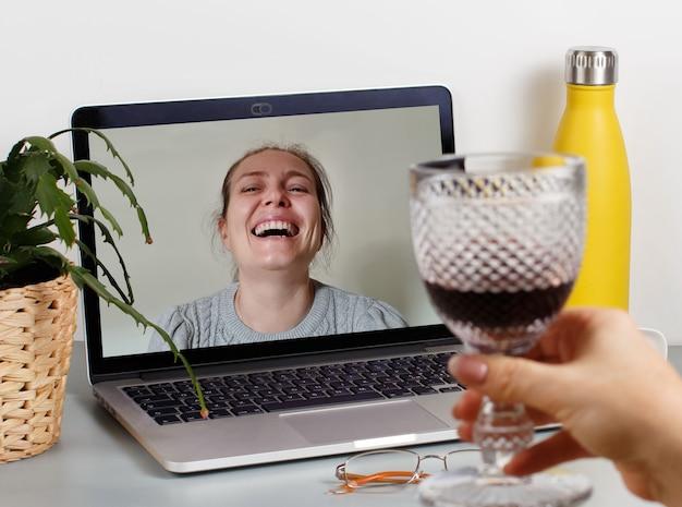 Due amici che bevono vino mentre hanno una videochiamata da vicino
