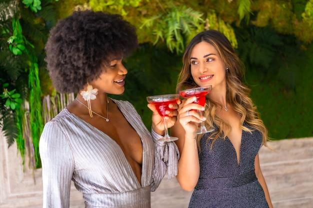 Due amici in abiti da gala con un cocktail a una festa in un hotel, stile di vita. stile di vita glamour, festa esclusiva
