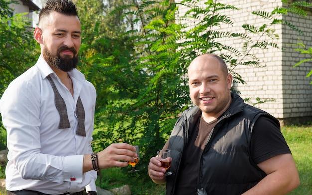 Due amici che bevono e parlano all'aperto