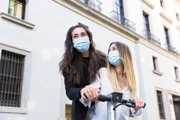 Due amici che si divertono su uno scooter elettrico. indossano maschere per il viso. concetto di nuova normalità.