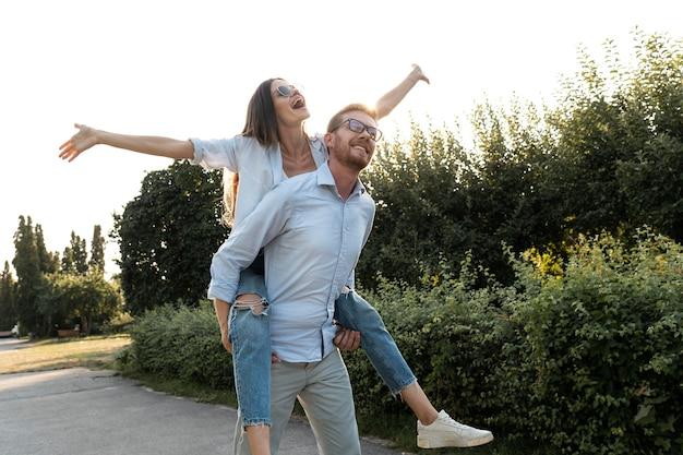 Due amici si divertono insieme all'aperto mentre cavalcano sulle spalle