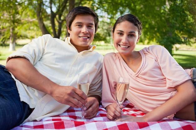 Due amici si sdraiano su una coperta mentre si tiene champagne