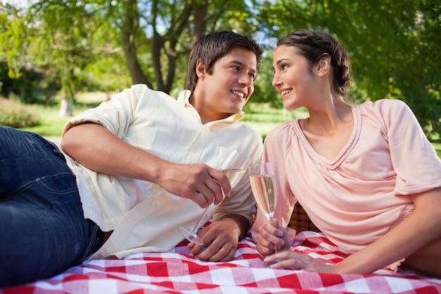 Due amici a guardare l'altro mentre si tiene gli occhiali durante un picnic