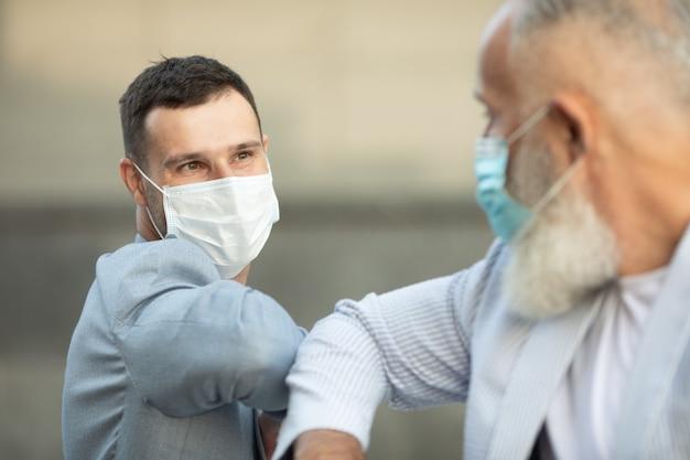Due amici con la maschera facciale si salutano con il gomito per strada