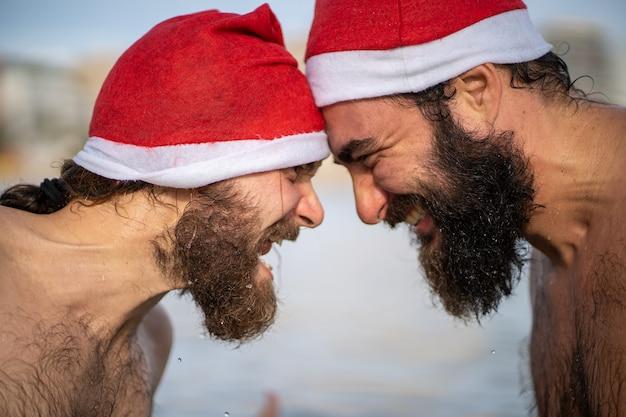 Due amici con il cappello di babbo natale stanno uno contro l'altro in una spiaggia a maiorca