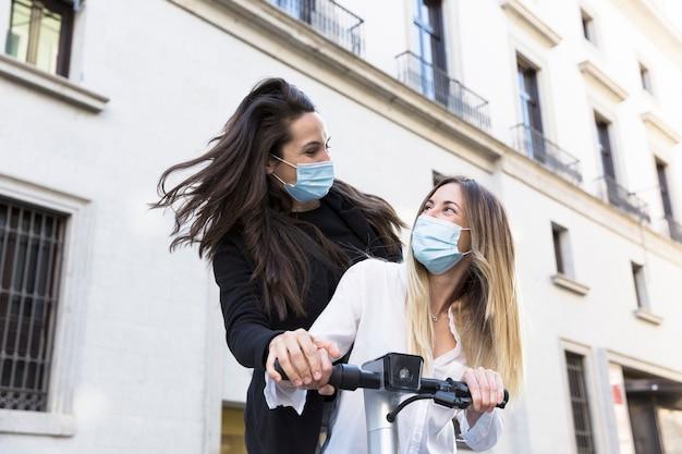Due ragazze divertenti su uno scooter elettrico. indossano maschere per il viso. concetto di nuova normalità.