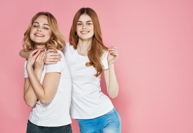 Due amiche divertenti in primo piano bianco di modo di fascino delle magliette